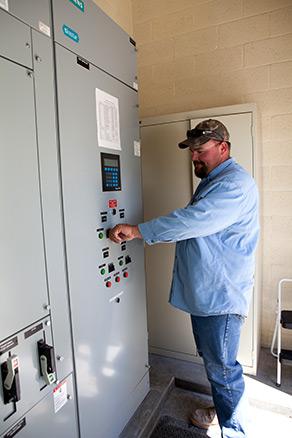 FHSD employee adjusting levels at pump station