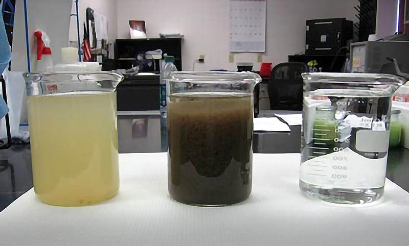 Containers of water showing the before, during and after the treatment process